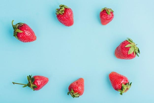 Blaue oberfläche mit rahmen von erdbeeren