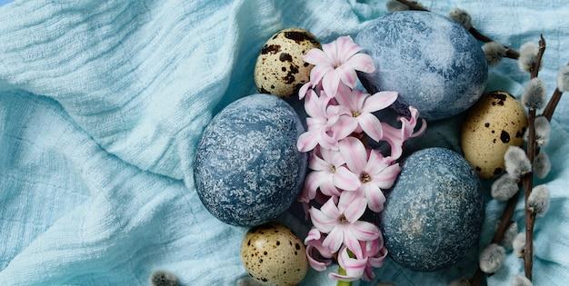Blaue ostereier auf blauem hintergrund. natürlich mit hibiskus bemalte eier mit marmorsteineffekt. öko-farbe. frohe osterkarte
