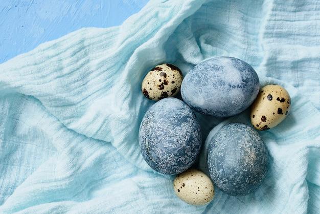 Blaue ostereier auf blauem hintergrund. natürlich mit hibiskus bemalte eier mit marmorsteineffekt. öko-farbe.