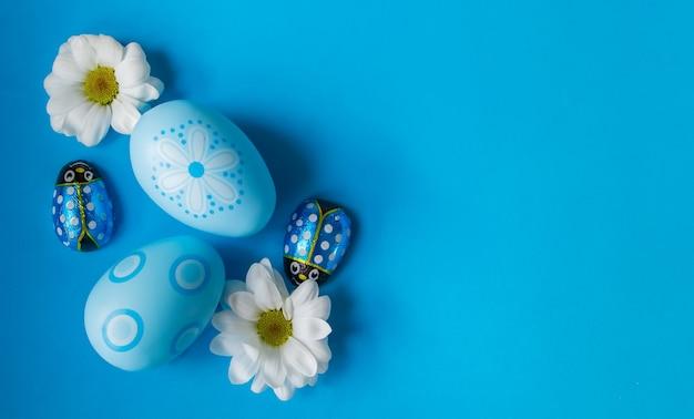 Blaue ostereier mit gänseblümchen und schokoladendamebags auf blauem hintergrund