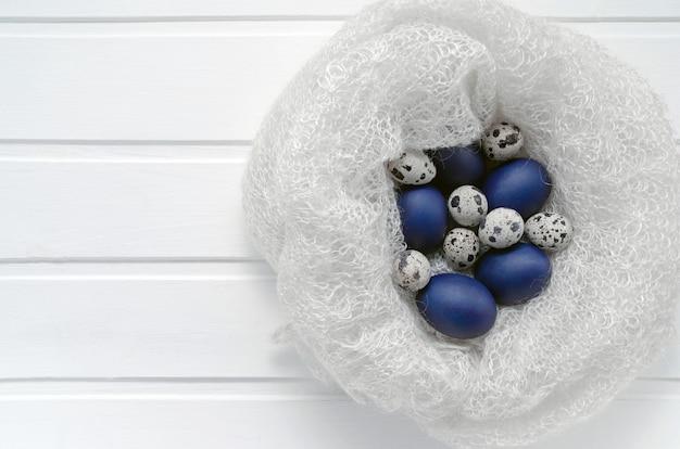 Blaue ostern- und wachteleier in einem schneeweißen wollnest auf einem weißen holz