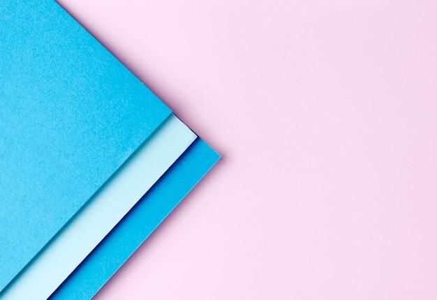 Blaue papiere auf rosa hintergrund
