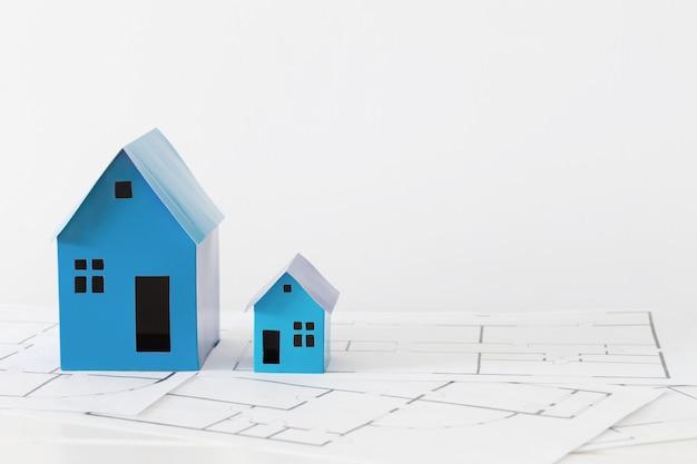 Blaue papierhäuser auf holztisch