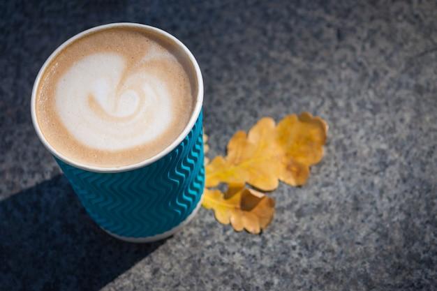 Blaue papierkaffeetasse auf den herbstfallblättern und dem steingrau