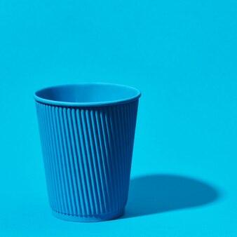 Blaue pappbecher stehend auf festem blau