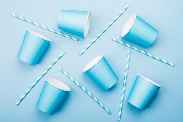 Blaue pappbecher und blau-weißes stroh auf blau