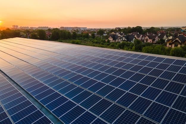 Blaue photovoltaik-sonnenkollektoren, die auf dem dach des gebäudes montiert sind, um bei sonnenuntergang sauberen ökologischen strom zu erzeugen. produktion eines erneuerbaren energiekonzepts.