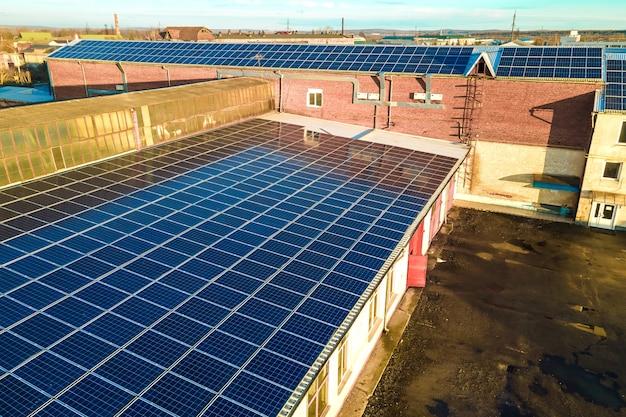 Blaue photovoltaik-sonnenkollektoren, die auf dem dach eines industriegebäudes montiert sind, um sauberen ökologischen strom zu erzeugen. produktion eines erneuerbaren energiekonzepts.