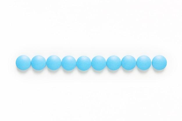Blaue pillendroge oder -tabletten des gesundheits- und medikamentenkonzeptes auf weiß mit kopienraum