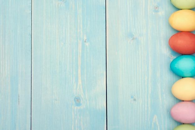 Blaue planke mit bunten ostereiern