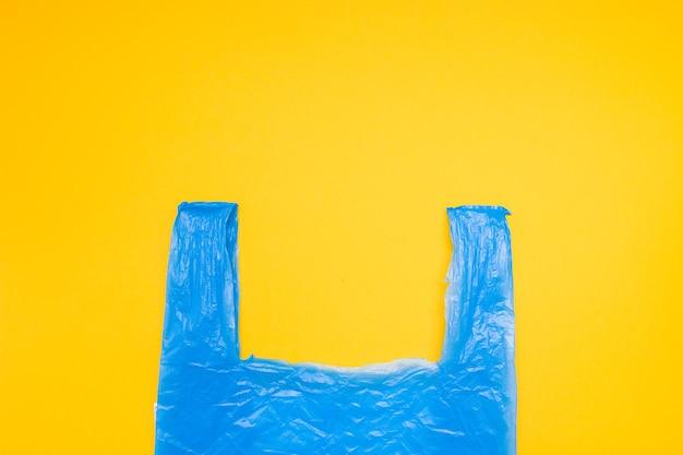 Blaue plastiktüte auf einem gelben hintergrundkopierraum, draufsicht