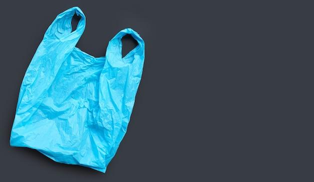 Blaue plastiktüte auf schwarzem hintergrund. speicherplatz kopieren