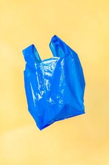 Blaue plastiktüte schwimmt mit einer gelben wand