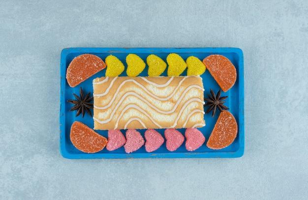 Blaue platte mit kuchenrolle mit anis und marmeladenstücken auf marmor.