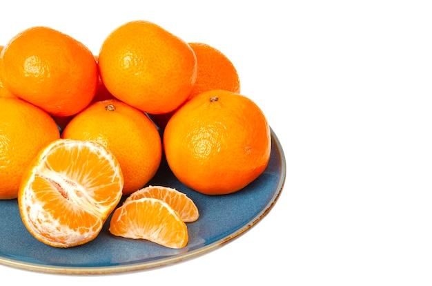 Blaue platte mit leuchtend orangefarbenen mandarinen isoliert