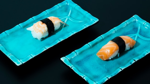 Blaue platten mit sushi auf einem schwarzen hintergrund