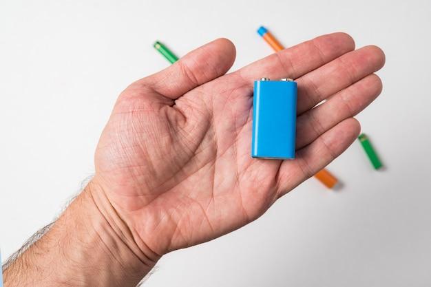 Blaue pp3-batterie in der männlichen hand auf weißem hintergrund. akkumulator