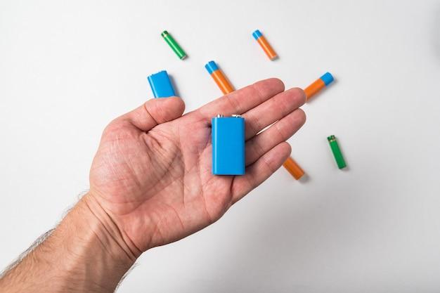 Blaue pp3-batterie in der männlichen hand auf weißem hintergrund. verschiedene arten von akkumulatoren.