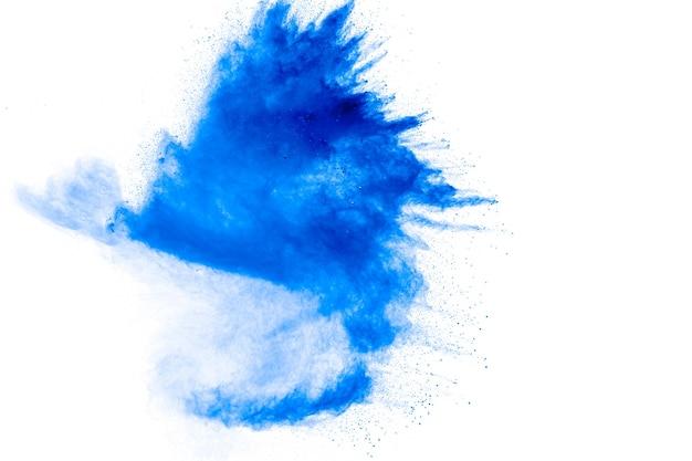 Blaue pulverpartikel spritzen auf weißem schwarzgrund.