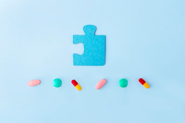 Blaue puzzleteile mit verschiedenen pillen und medikamenten. konzept der behandlung neurologischer erkrankungen: autismus, alzheimer, dimension. kopieren sie platz für text. bewusstseinstag. unterstützung und akzeptanz.