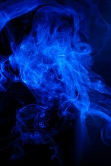 Blaue rauchbewegung auf schwarzer oberfläche.