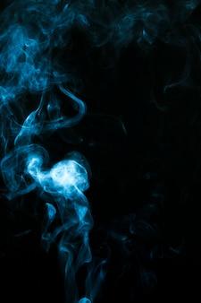 Blaue rauchwolken über schwarzem hintergrund