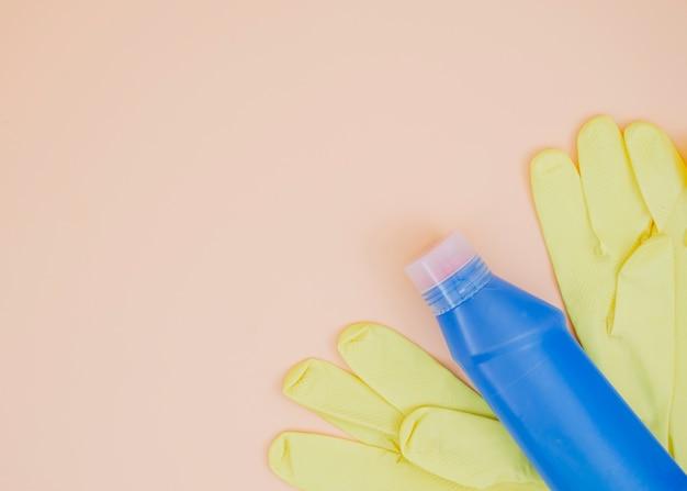 Blaue reinigungsmittelflasche mit gelben handschuhen auf pfirsichhintergrund