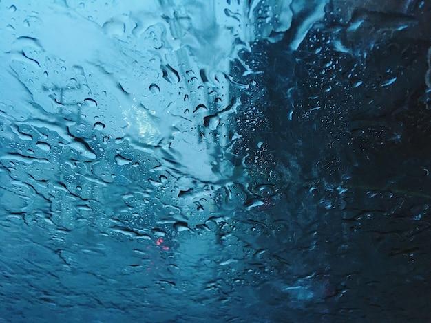 Blaue ruhige ruhe des kühlen tones der starken regenzeit innerhalb der autoansicht vom windschutzscheibenglashintergrund