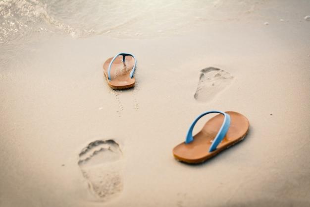 Blaue sandale mit abdruck auf der strandkonzeptzeit zu reisen