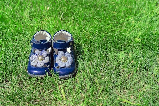 Blaue sandalen für kinder auf grünem gras. die schuhe des netten mädchens im garten. das konzept von kindheit und sommer