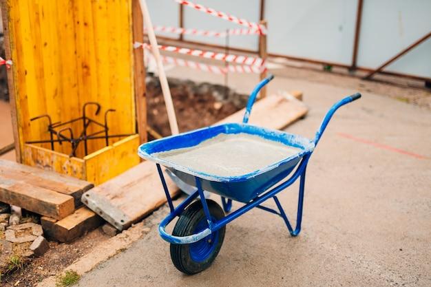 Blaue saubere neue schubkarre für zement. den ersten schaufelzement in das fundament auf den bau des hauses legen.