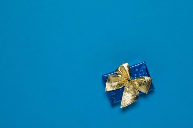 Blaue schachtel mit einem geschenk in einem goldenen band. ein überraschungsgeschenk.