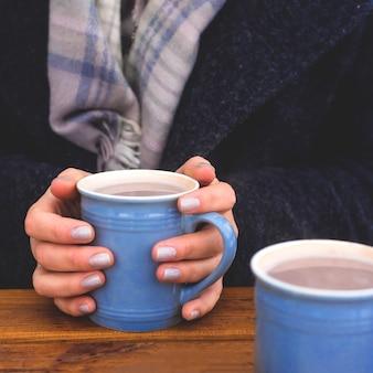 Blaue schale kakao in den weiblichen händen auf der terrassenwintertabelle.