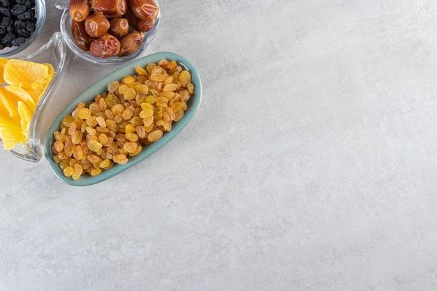 Blaue schalen mit getrockneten aprikosen, schwarzen und goldenen rosinen auf steinhintergrund.