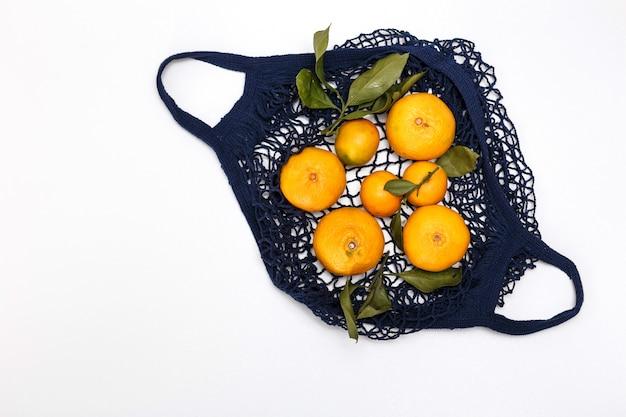 Blaue schnurtasche mit mandarinen auf einem weißen hintergrund