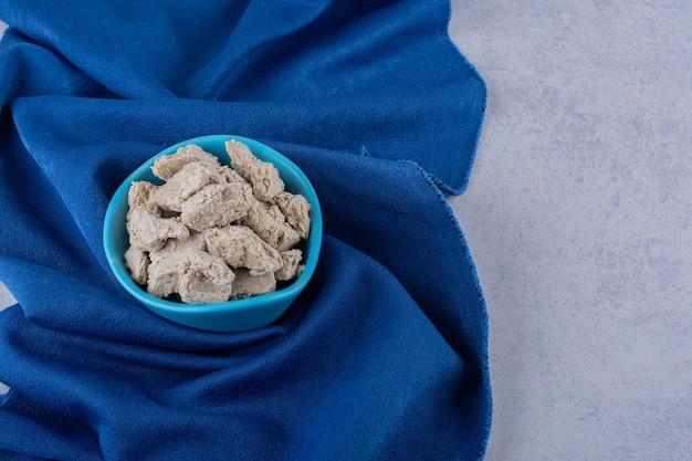 Blaue schüssel der leckeren sonnenblumenhalva auf steintisch.