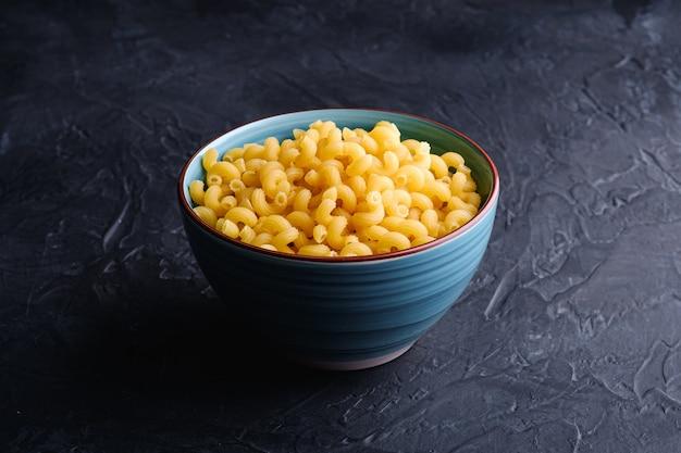 Blaue schüssel mit cavatappi ungekochten goldenen weizen-lockigen nudeln auf strukturiertem dunkelschwarzem hintergrund, winkelansicht