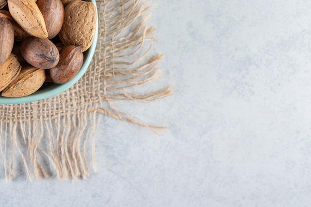 Blaue schüssel mit geschälten mandeln und walnüssen auf steinhintergrund.