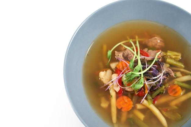 Blaue schüssel mit gesunder appetitlicher gemüsesuppe