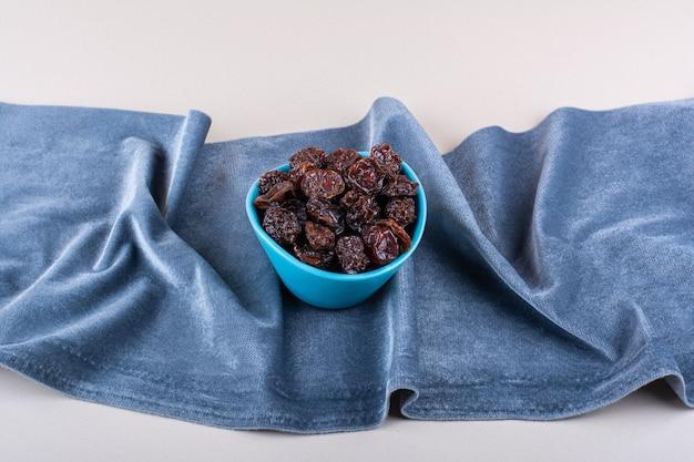 Blaue schüssel mit getrockneten bio-pflaumen auf weißem hintergrund. foto in hoher qualität
