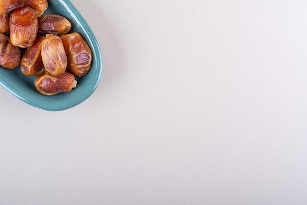 Blaue schüssel mit getrockneten leckeren datteln auf weißem hintergrund. foto in hoher qualität