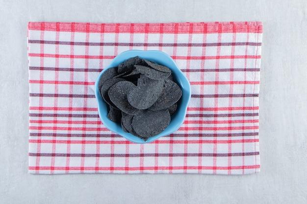 Blaue schüssel mit knusprigen schwarzen chips und tischdecke auf stein.