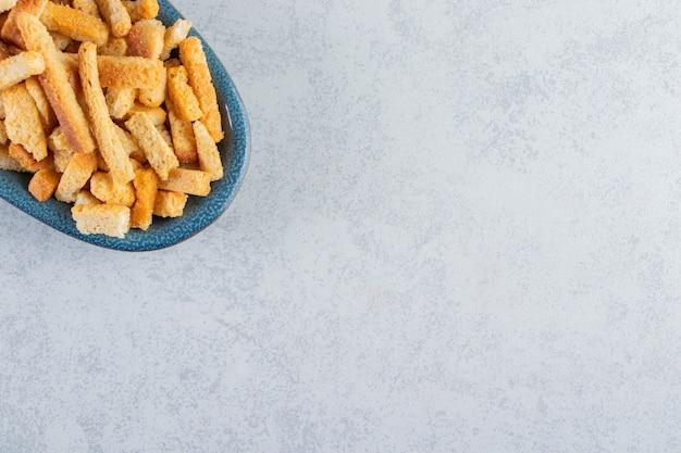 Blaue schüssel mit leckeren knusprigen crackern auf steinhintergrund.