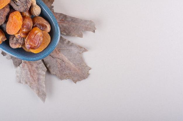 Blaue schüssel mit verschiedenen organischen nüssen und früchten auf weißem hintergrund. foto in hoher qualität