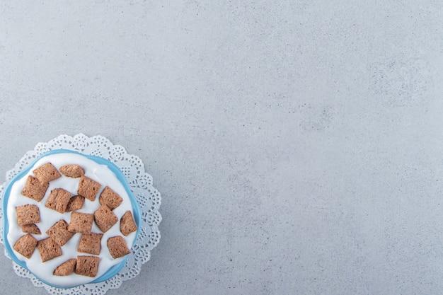 Blaue schüssel schokoladenpads cornflakes mit sahneschaum. foto in hoher qualität
