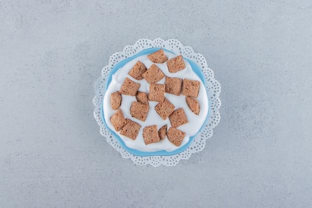 Blaue schüssel schokoladenpads cornflakes mit sahneschaum
