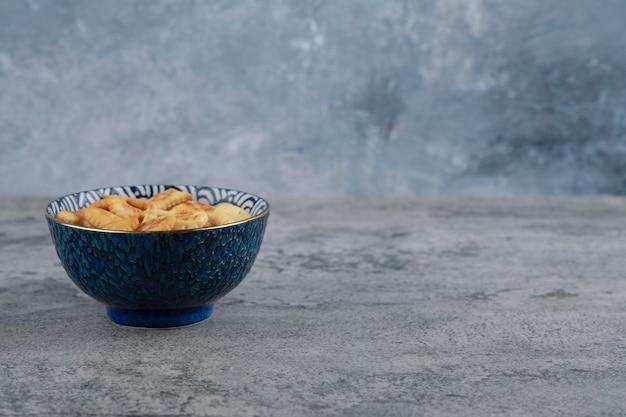 Blaue schüssel voll von verschiedenen gesalzenen crackern auf marmorhintergrund.
