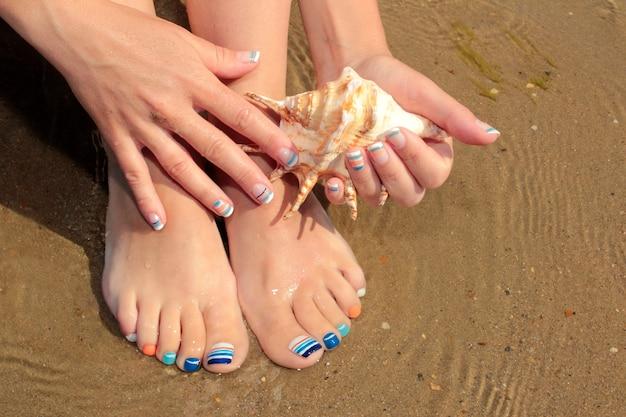 Blaue sommerliche französische maniküre und hände, die muscheln auf dem sand halten