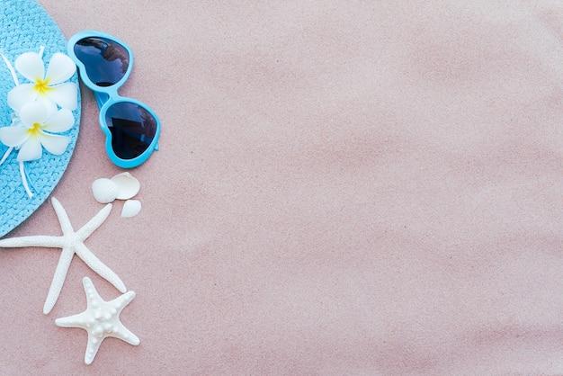 Blaue sonnenbrille, starfish, blume und blauer hut setzen auf hintergrund des sandigen strandes auf den strand