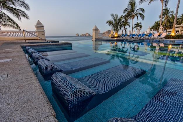 Blaue sonnenliegen auf schwimmbad